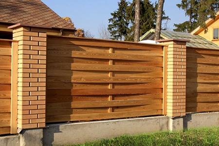 Плетеный забор из досок с кирпичными столбами
