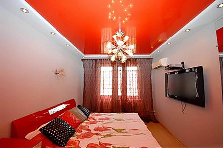 Красный глянцевый потолок в спальне